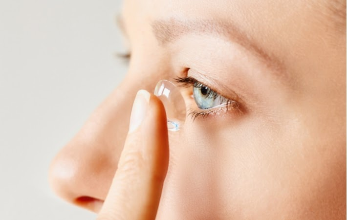 A close up on someone's eye who is putting in a scleral contact lens to help treat dry eye