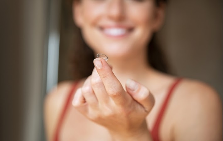 A woman reaching out her arm holding a contact lens on her fingertip